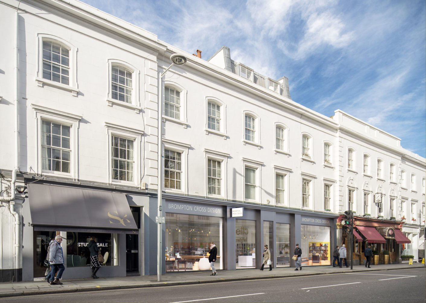 Image of retail stores on Fulham Road with CGI imagery showing 3 stores as one new shopfront in grey