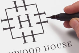 Highwood House logo during the design process with a hand and pen making finishing touches
