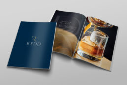 Redd Real estate brochure inside page of a whiskey glass next to a closed brochure