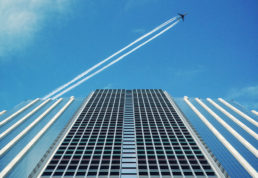 CGI image looking up at a skyscraper with a plane flying over with vapour trail
