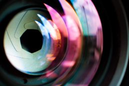 Close up photograph of a camera lens reflecting in the light