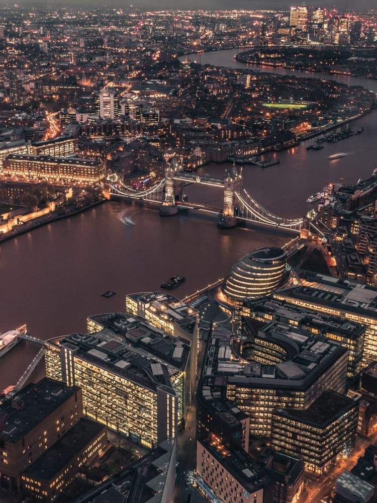 Aerial photograph of london at night overlooking the thames and tower bridge