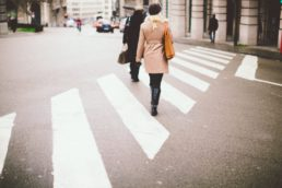 Photograph of a lady and man crossing a zebra crossing in London
