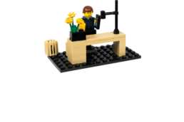 Lego man at desk with mobile phone