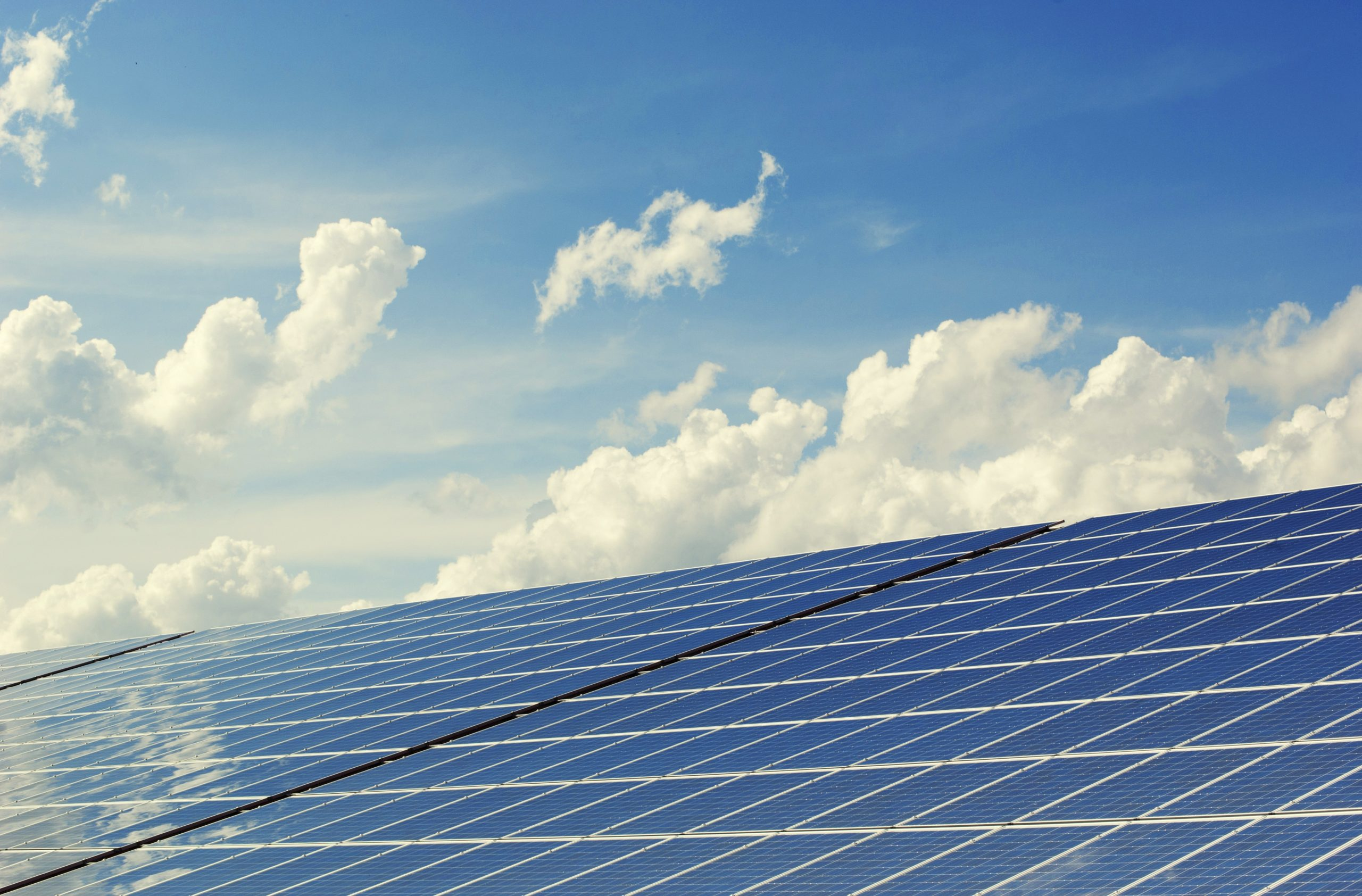 solar panels beneath a blue sky with fluffy clouds